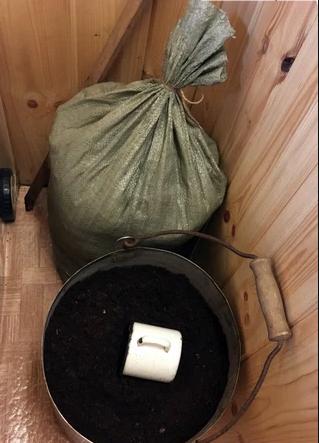 Просеянный и просушенный торф в бачке и в мешке рядом.